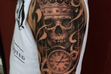 23 tribal skull tattoo with a clock on an arm