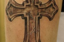 23 voluminous cross tattoo on an arm