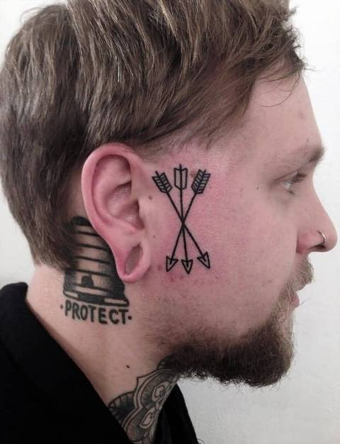 Three arrow tattoos on the face