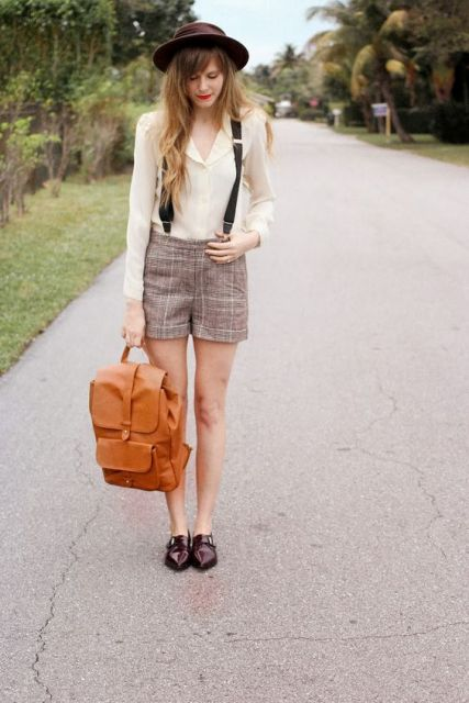 With beige blouse, checked shorts, brown leather backpack and brown hat
