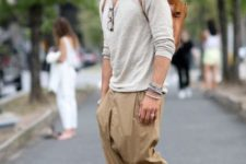 With beige loose shirt, brown leather backpack and loafers
