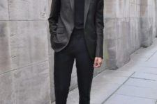 With black shirt, gray jacket and black shoes