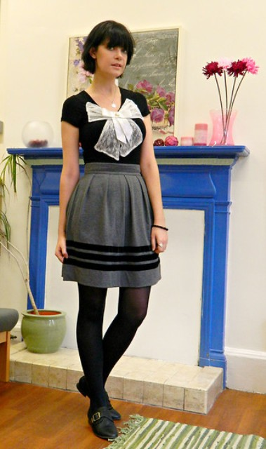 With black shirt with white bow, gray skirt and black tights