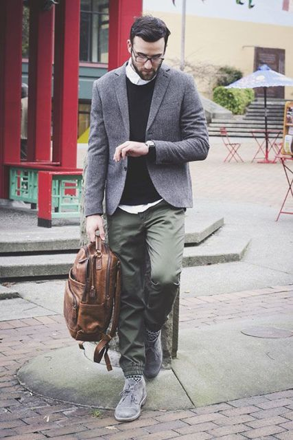 With black sweatshirt, gray jacket, brown backpack and gray sneakers