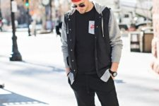 With black t-shirt, gray and black jacket, red printed cap and red sneakers