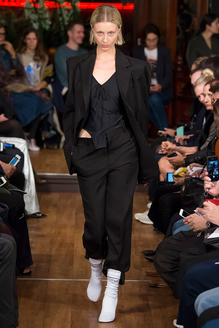 With black top, trousers and long blazer