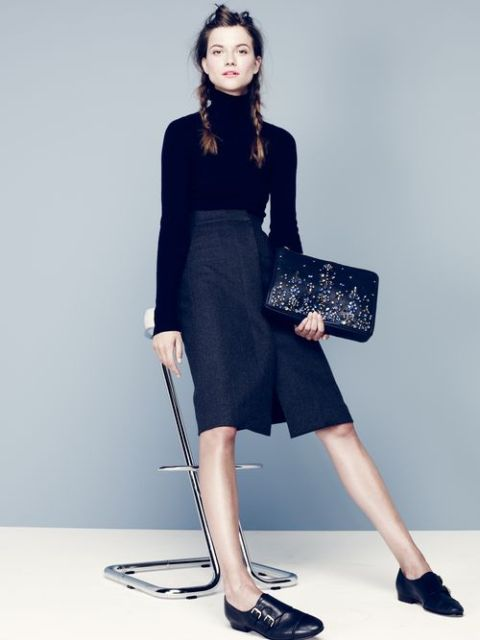 With black turtleneck, knee-length skirt and printed clutch