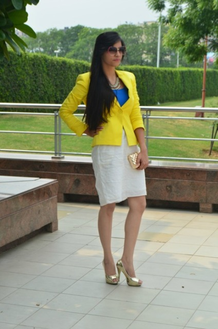 With blue shirt, white skirt, metallic shoes and clutch