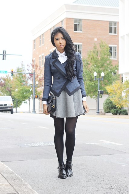 With gray and black jacket, light gray skirt and black clutch
