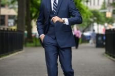 With navy blue suit, white shirt and striped tie