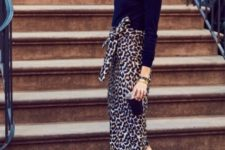With navy blue turtleneck and black pumps