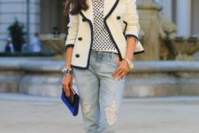 With polka dot shirt, black and white blazer, cuffed jeans and cobalt blue clutch