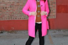 With printed sweatshirt, black pants and hot pink coat