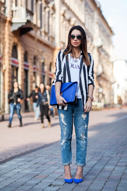 With striped jacket, blue clutch and distressed jeans