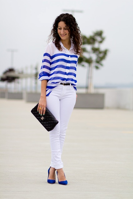 With striped loose blouse, white pants and black clutch