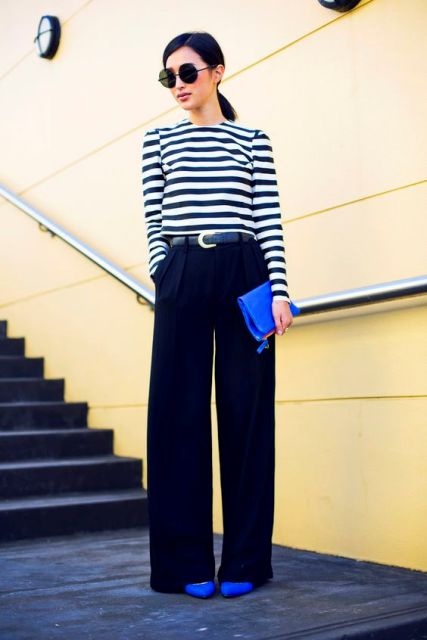 With striped shirt, black wide leg trousers and clutch