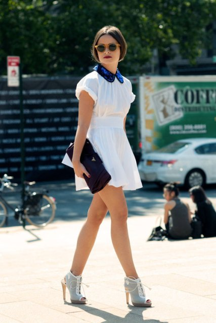 White cut-out boots a with white mini dress with blue collar and black clutch