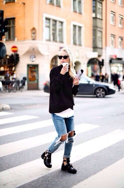With white shirt, black sweater and distressed jeans