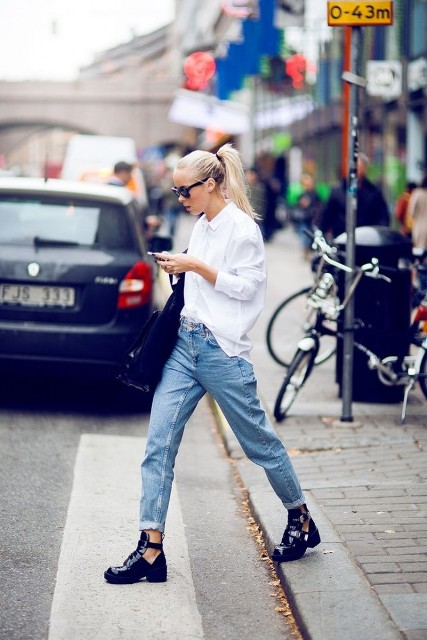 With white shirt, cuffed jeans and bag
