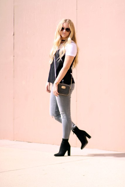 With white t shirt, black top, gray pants and small bag