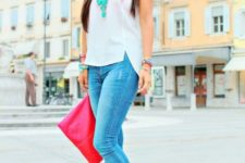 With white top, cuffed jeans and pink clutch