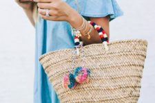 a denim ruffle dress, a woven tote with pom poms, and leather sandals