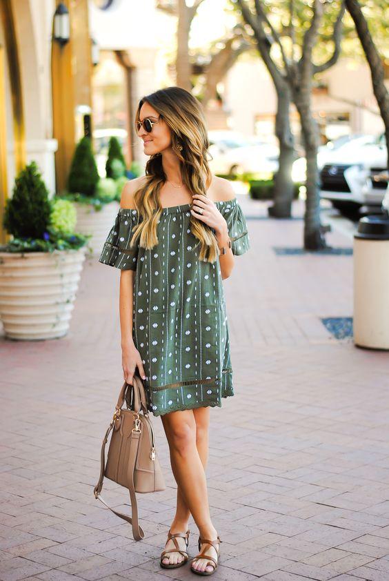 green printed off the shoulder dress, brown sandals and a handbag