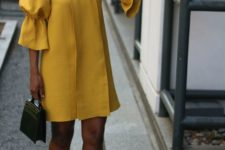 off the shoulder exaggerated sleeve yellow dress, black heels and a small handbag