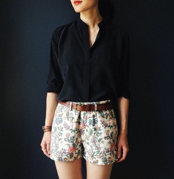 a black shirt, floral shorts and a leather belt