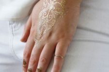 02 delicate gold henna tattoo on the hand and fingers