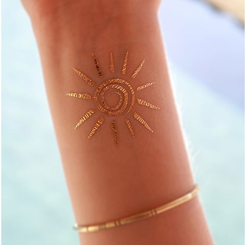 gold henna sun tattoo on the wrist