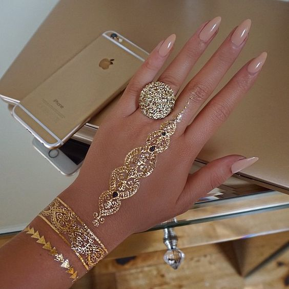 gorgeous gold glitter tattoo on the hand and two tattoo bands on the wrist