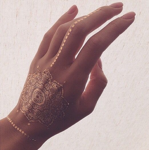 gorgeous mandala gold henna tattoo on the hand, finger and wrist