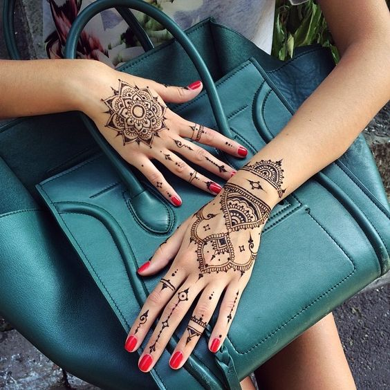 gorgeous mandala tattoo on one hand and paterns on the other
