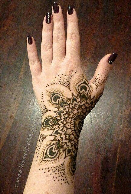 half mandala with feathers tatoto on a wrist and hand