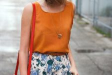 11 a bold orange sleeveless top and blue floral shorts