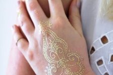 11 delicate gold henna tattoo on the hand