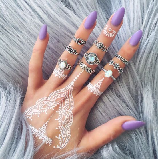 lacey white henna tattoo on the hand and fingers