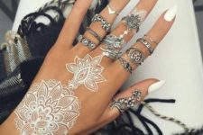 12 lacey white henna tattoo on the hand and white manicure