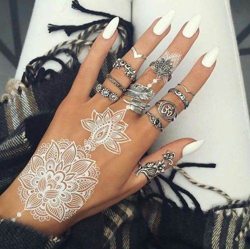 lacey white henna tattoo on the hand and white manicure