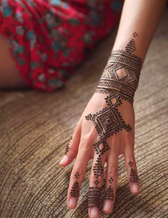 Moroccan inspired henna tattoo on fingers, hand and wrist