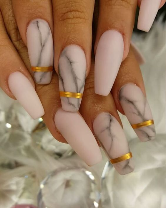 matte pink marble nails with accent metallic stripes