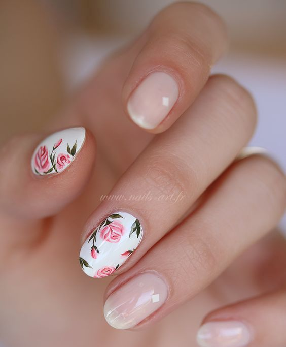 nude manicure with two white and pink rose nails
