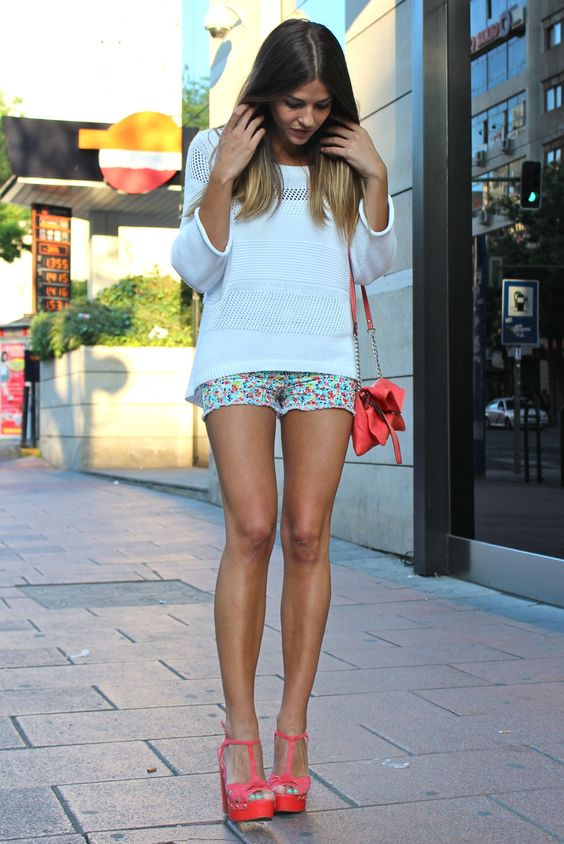 colorful floral shorts, a crocheted white top, coral platform shoes and a bag
