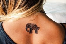 17 a small elephant tattoo on the upper part of the back