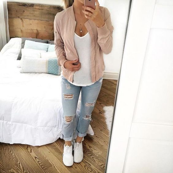 a white tee, distressed denim, a blush bomber and white sneakers