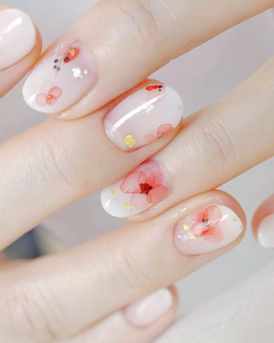 glossy white nails with natural-looking red flowers