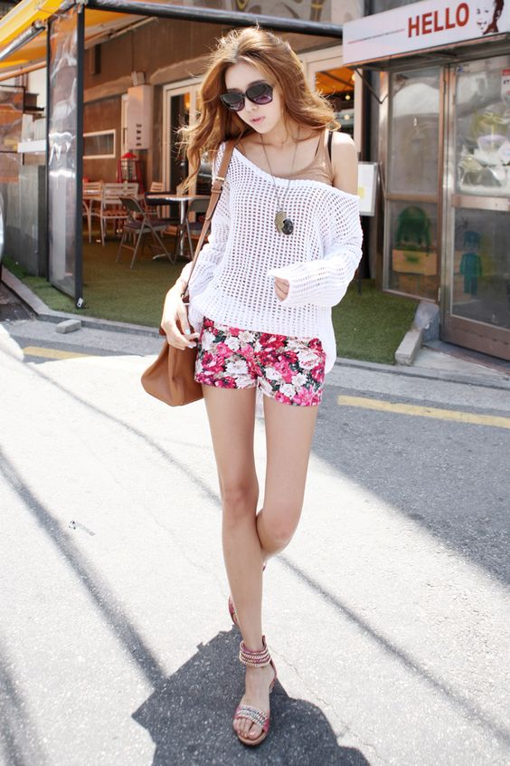 pink floral shorts, a nude top, a white crochet top over it and sandals