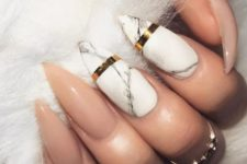 18 stiletto nude nails and two marble ones with accent gold stripes