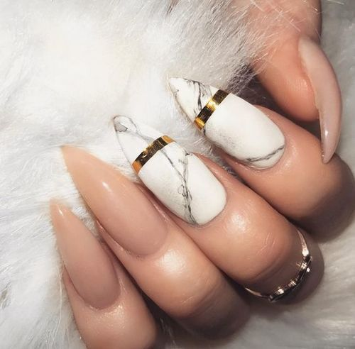 stiletto nude nails and two marble ones with accent gold stripes